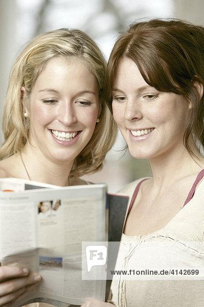 Zwei junge Frauen lesen in einer Zeitschrift