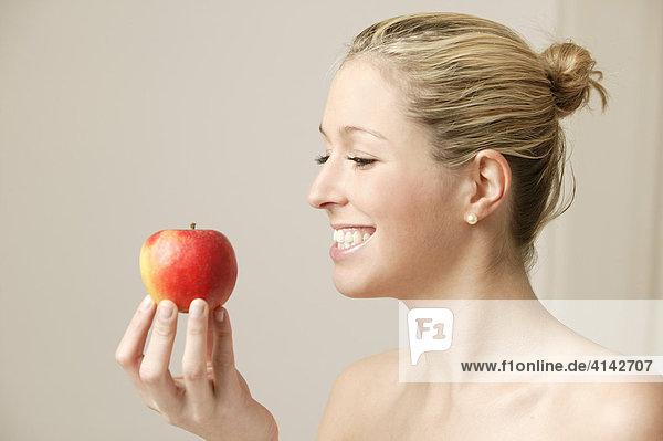 Junge  blonde Frau mit Apfel  lächelnd
