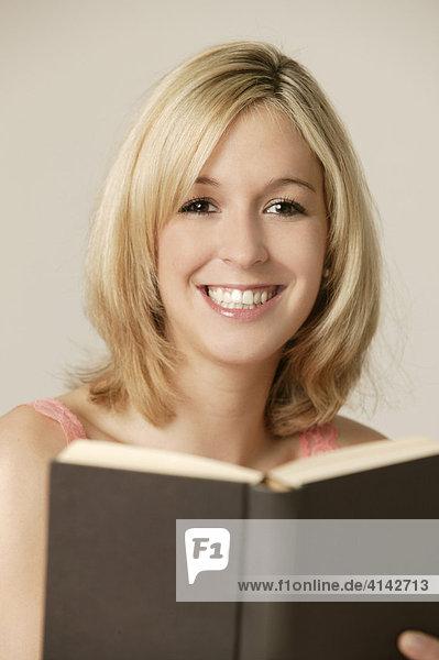 Junge  blonde Frau liest Buch  lächelt