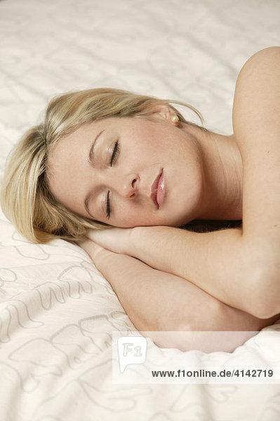 Junge  blonde Frau liegt im Bett  schläft  Nahaufnahme