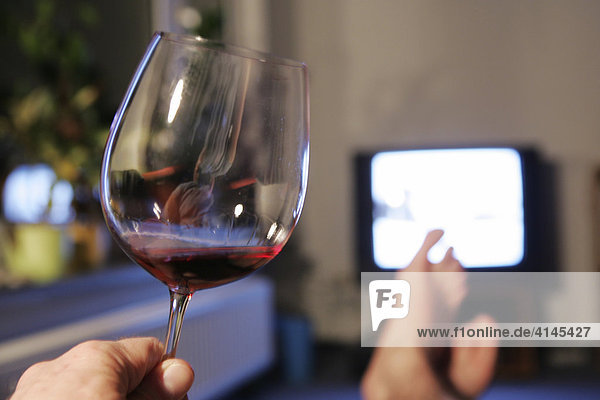 DEU  Germany : man in front of an TV. Glas of red wine.