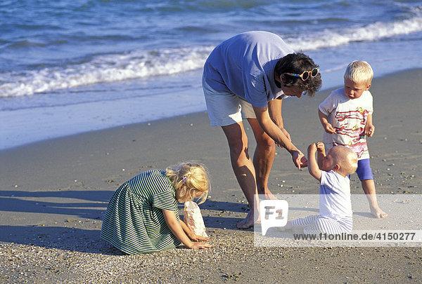 Mutter mit Kindern sammelt am Strand Muscheln