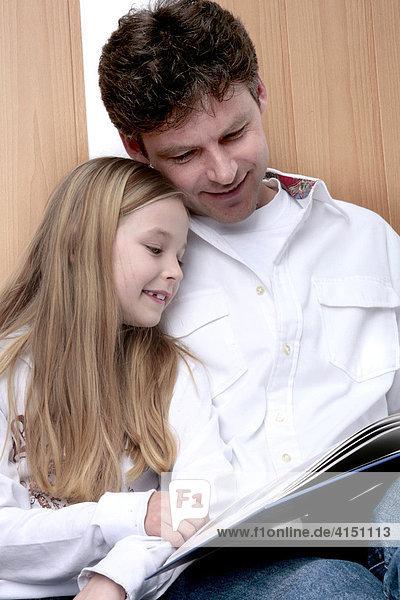 Vater und Tochter lesen in einem Buch