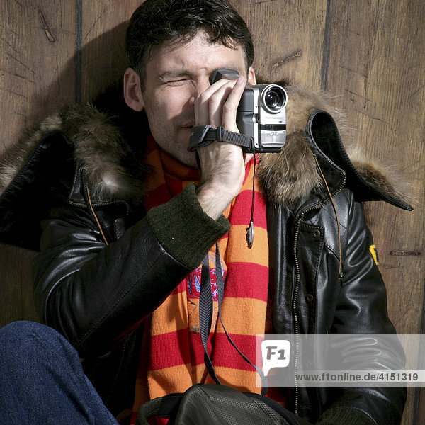 Young man wearing a scarf filming with a video camera