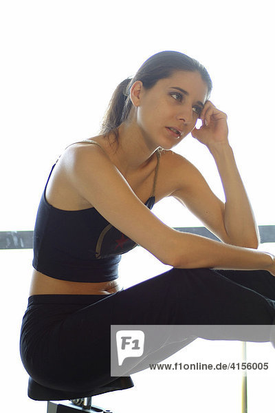 Portrait of a young woman exercising at home on an exercise bike