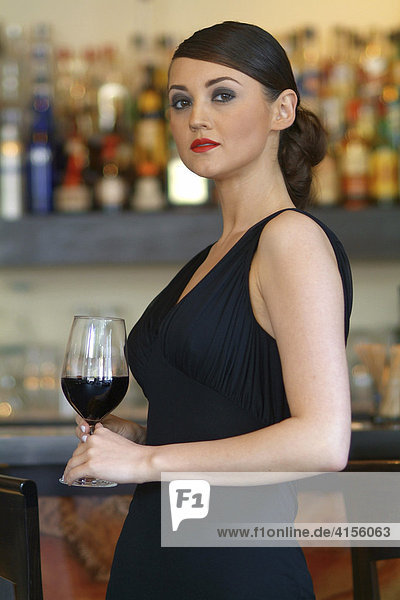 Young woman wearing a black evening dress drinking a glass of red wine at the bar