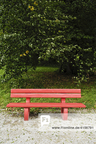Leere rote Parkbank
