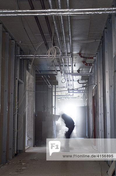 Bauarbeiter verlegt Leitungen in einem Rohbau