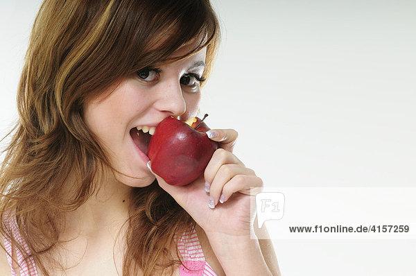 Hübsche junge braunhaarige Frau beißt in einen roten Apfel
