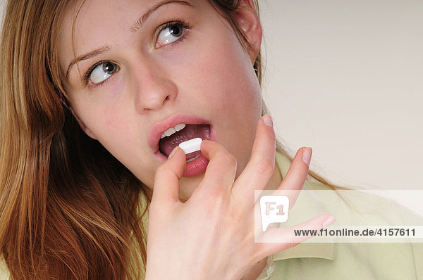 Young long-haired woman wearing green polo shirt taking a pill to alleviate her headache