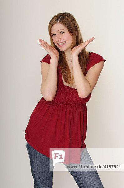 Junge  langhaarige Frau mit rotem Top ist fröhlich