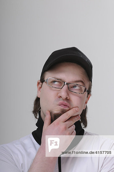 Young man with a goatee  wearing glasses and a black baseball cap  looking pensive