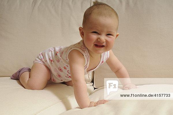 Baby in Unterhemd  Body  7 Monate  auf Sofa  krabbelt  Vierfüßlerstand  lacht fröhlich