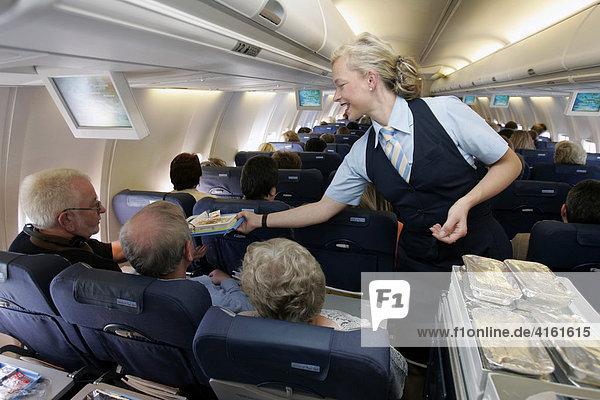 Flugbegleiterin beim Service in der Flugzeugkabine.(Pressetermin)