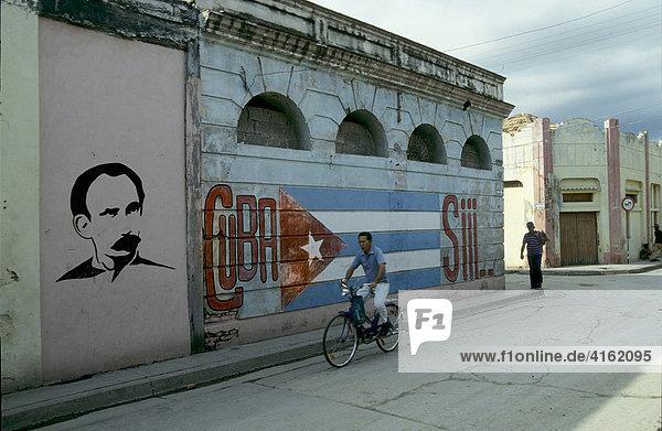 Radfahrer in den Straßen von Havanna mit der Kubaflagge,  gemalt an einer Hauswand,  Kuba