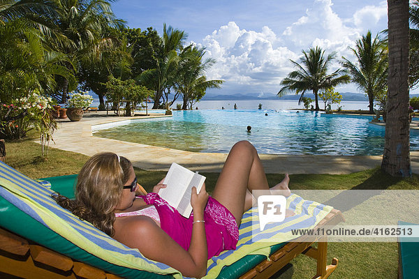 Gangga Island the pool area. A Woman is reading a book  island with a hotel in the north of Sulawesi  Indonesia.