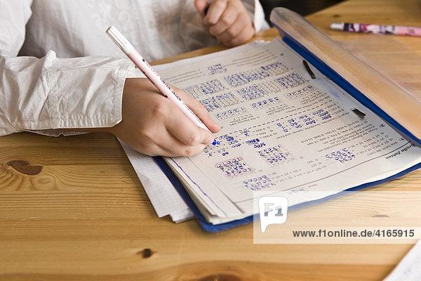 Young schoolgirl doing homework in nursery  mathematics exercises