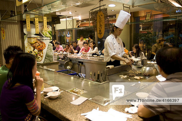Koch bereitet das Essen am Tisch zu  Singapur  Südostasien