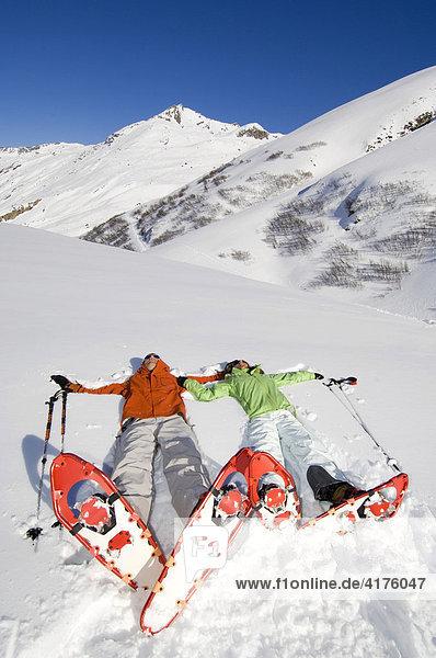 Im Schnee liegendes Paar während Schneeschuhtour  Bielerhöhe  Galtür  Tirol  Österreich