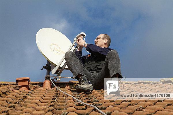 Mann instaliert satellitenschüssel
