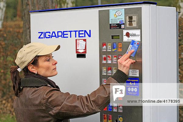 Eine junge Frau holt Zigaretten am Zigarettenautomat. In der rechten Hand hält sie eine EC-Karte zur Alterskennung die in den Automat eingesteckt wird.