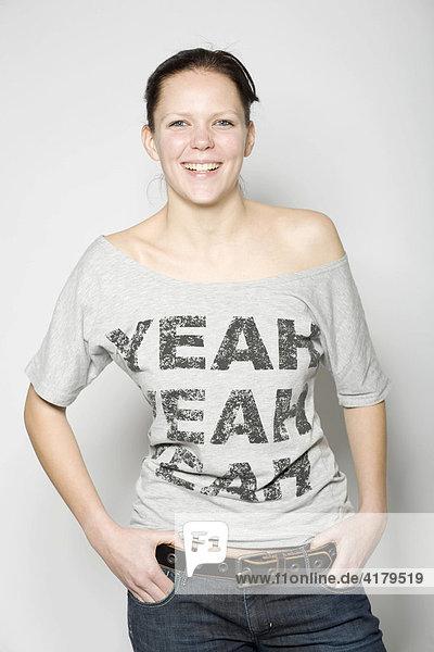 Lachende junge Frau mit Händen in den Taschen vor grauem Hintergrund