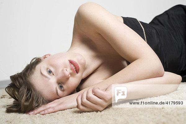 Portrait einer jungen  auf einem Teppich liegenden Frau
