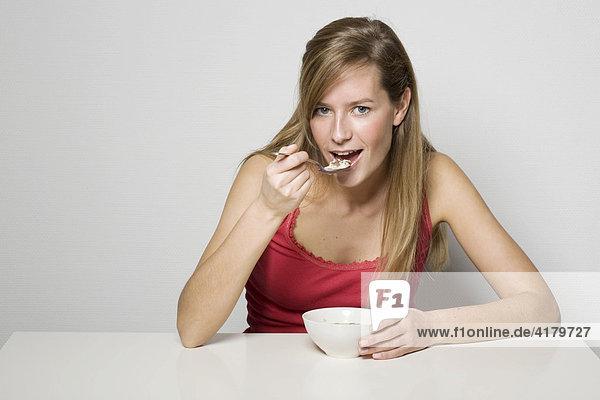 Junge Frau sitzt am Tisch und ißt Müsli