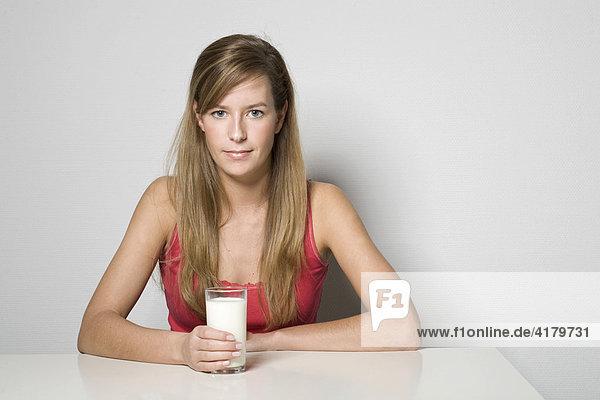 Junge Frau sitzt an einem Tisch und hält ein Glas Milch in der Hand
