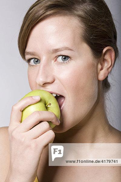 Junge Frau beißt in einen grünen Apfel