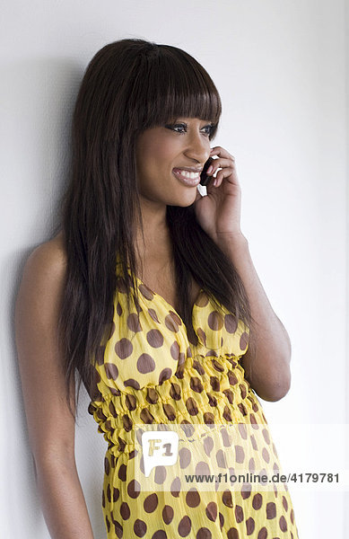 Young dark-skinned woman leaning against a wall talking on the phone
