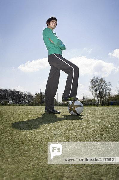 Junge Frau steht mit verschränkten Armen auf einem Sportplatz  hat ein Bein auf einen Fußball gestellt