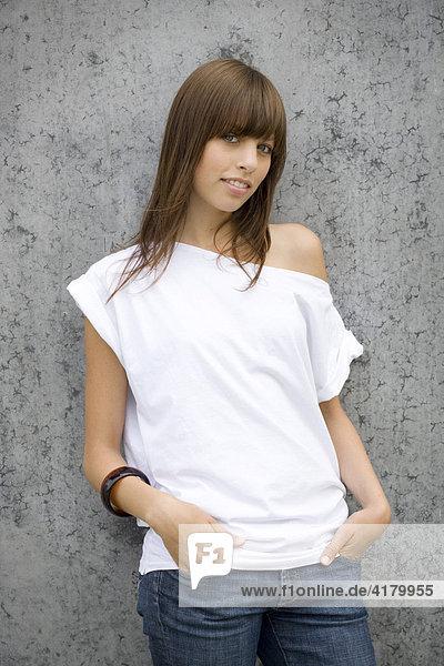 Junge dunkelhaarige Frau steht mit Jeans und weißem Top vor einer Wand und blickt entspannt in die Kamera