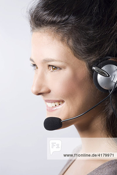 Profile of a young woman with dark hair smiling while phoning on a headseat