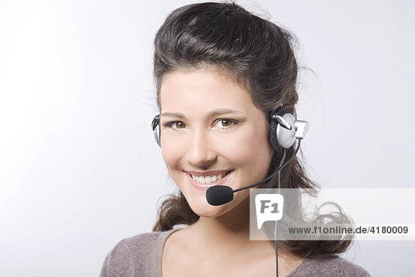 Junge dunkelhaarige Frau lacht beim Telefonieren mit Headset