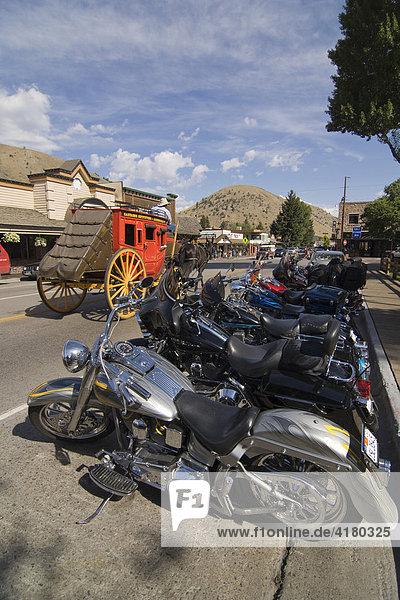 Harley Davidson Motorräder stehen geparkt in Jackson  hinten fährt eine Postkutsche  Wyoming  Vereinigte Staaten von Amerika
