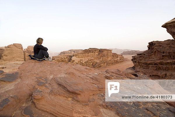 Frau sitzt auf Felsvorsprung und blickt in die Ferne  Wadi Rum  Jordanien  Naher Osten
