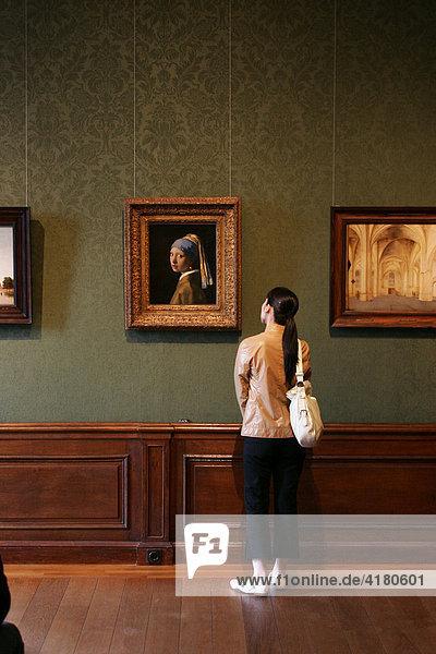 Besucherin betrachtet das berühmte Gemälde Das Mächen mit dem Perlenohrring des holländischen Malers Johannes Vermeer im Mauritshuis in Den Haag Niederlande