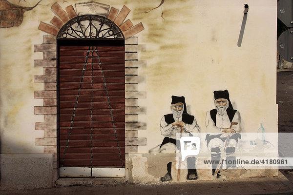 Wandbild mit sitzenden älteren Maennern in Tracht in Cala Gonone auf Sardinien  Italien  Europa