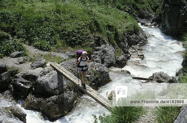 Wanderer überquert den Vomper Bach im Karwendelgebirge  Karwendel  Tirol  Österreich
