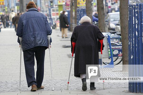 Zwei alte Leute auf Krücken von hinten