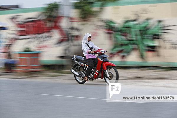 Mädchen auf Motorrad in Tenggarong  Ost-Kalimantan  Borneo  Indonesien