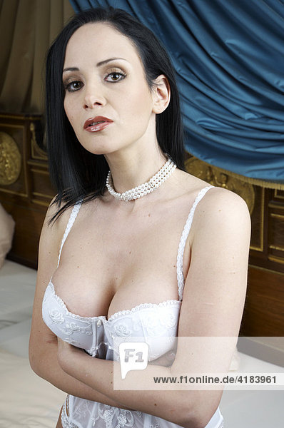 Young woman in an erotic pose in a hotel suite