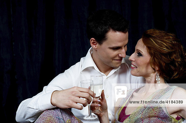 Couple dressed in evening wear  caressing one another