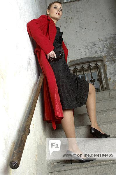 Junge Frau in rotem Mantel blickt sich um im Treppenhaus