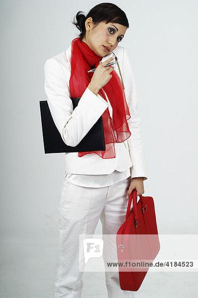 Junge Frau mit roter Tasche telefoniert mit Handy