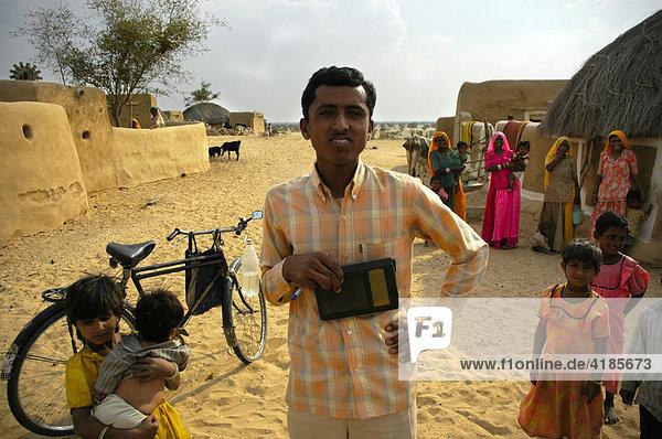 Junger Mann mit Radio und Fahrrad in einem Dorf mit vielen Menschen  Wüste Thar bei Jaisalmer  Rajasthan  Indien  Asien