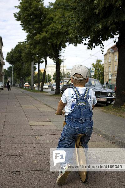 Eine Strassenidylle in Potsdam  Deutschland mit kleinem Jungen der ein Laufrad fährt