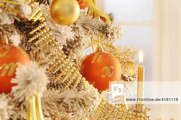 Geschmückter Weihnachtsbaum mit brennender Kerze