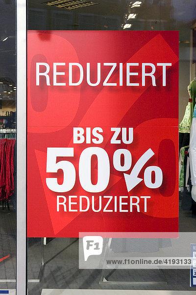 Ein Schild in einem Schaufenster  Werbung für reduzierte Ware